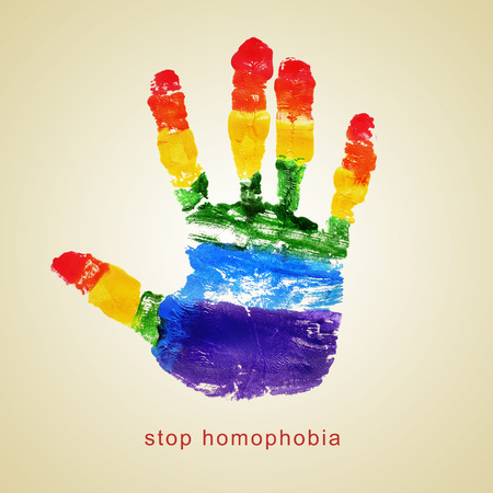 rainbow print: text stop homophobia and a handprint with the colors of the rainbow flag on a beige  Stock Photo