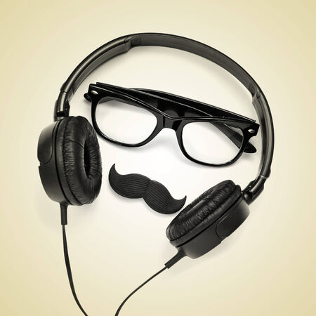 millennial: a pair of glasses, a mustache and a pair of headphones on a beige background, depicting a hipster guy