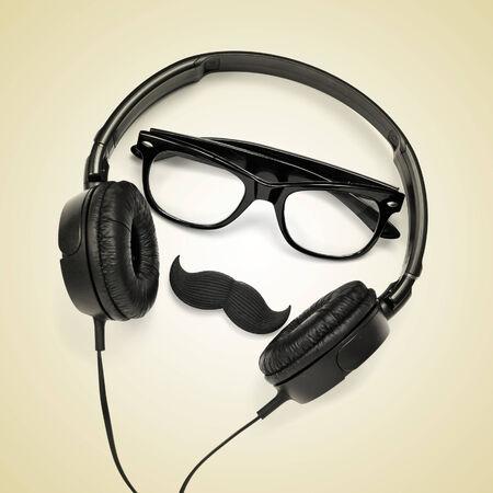caricaturas de personas: un par de anteojos, un bigote y un par de auriculares en un fondo de color beige, que representa a un hombre inconformista