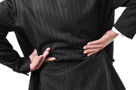 spinal disc herniation: man wearing a suit with his hands in his low back because of his low back pain