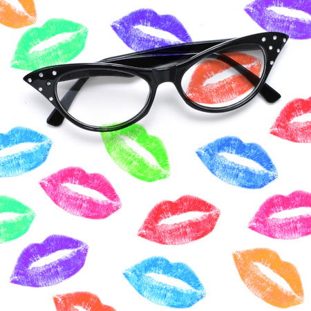 a pair of eyeglasses and a lipstick marks of different colors on a white background photo