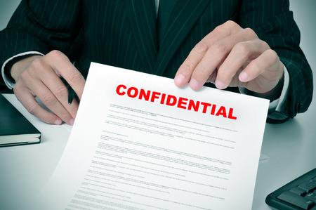 un uomo che indossa un abito che mostra un documento con il testo confidenziale scritto in esso