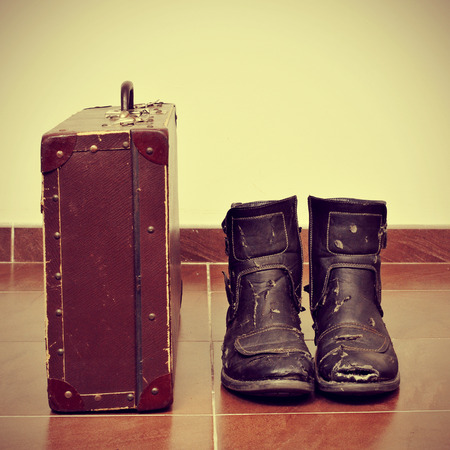 old shoes: picture of an old suitcase and a pair of worn boots with a retro effect