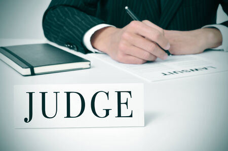 personal injury: a man wearing in his desk with a nameplate in front of him with the word judge written in it Stock Photo