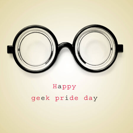 a pair of nearsighted glasses and the sentence happy geek pride day on a beige background photo