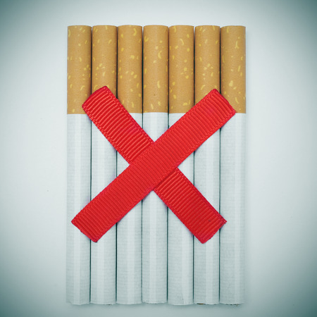 a pile of cigarettes and two crossed red slashes, depicting the concept of no smoking photo