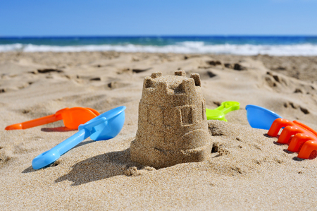 sandcastle: a sandcastle and toy shovels on the sand of a beach