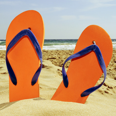 a pair of orange flip-flops on the sand of a beach photo