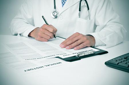 historia clinica: un m�dico en su oficina revisando algunas documentos