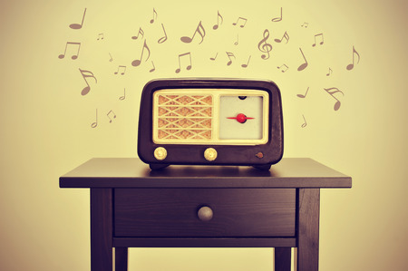 transistor: an antique radio receptor on a desk and musical notes, with a retro effect