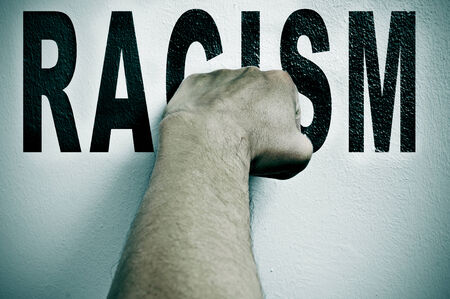 elimination: a man punching the word racism, depicting the concept of the fight against racism