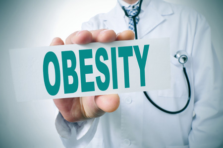 fat person: a doctor showing a signboard with the word obesity written in it