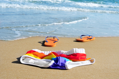 rainbow swimsuit and orange flip-flops in the sand of a beach
