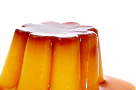 closeup of a creme caramel topped with caramel sauce on a white background photo