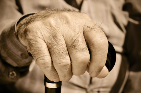 gerontology: closeup of the hand of an old man with a walking stick