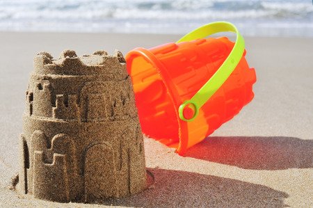 an orange toy bucket and a sandcastle on the sand of a beach photo