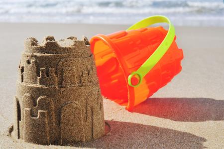 sand mold: an orange toy bucket and a sandcastle on the sand of a beach