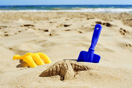 sand mold: a sand starfish and some toy shovels on the sand of a beach