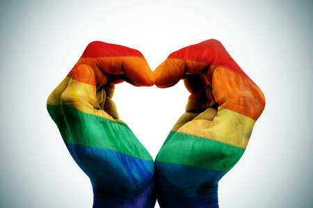man hands patterned as the rainbow flag forming a heart, symbolizing gay love Stock Photo