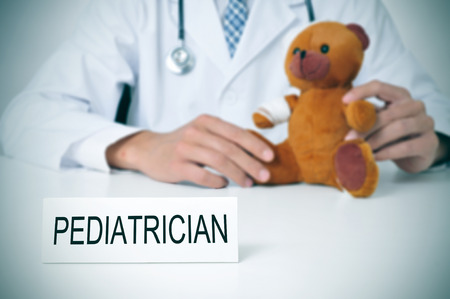 paediatrician: a doctor sitting in a desk with a injured teddy bear and a nameplate with the word pediatrician written in it