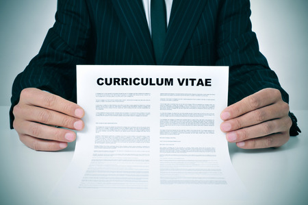 a man wearing a suit showing his curriculum vitae photo