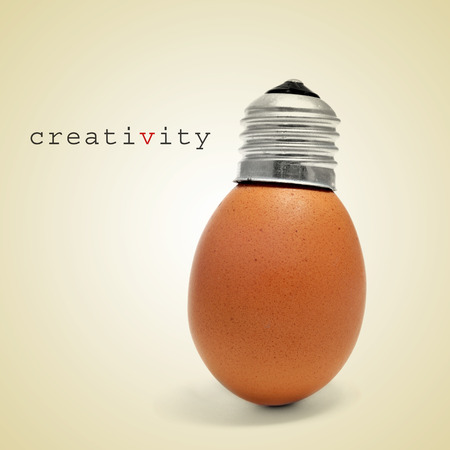 word creativity and an egg with a screw cap like a light bulb on a beige background photo
