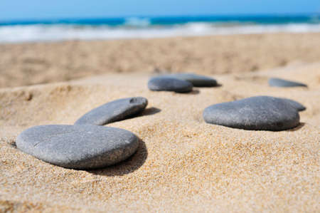 chill out: closeup of some gray flat stones on the sand of a beach Stock Photo
