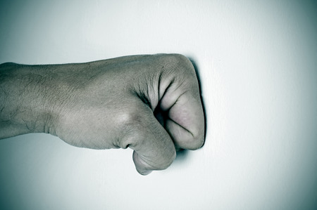 competitividad: hombre pu�o que perfora una superficie blanca Foto de archivo