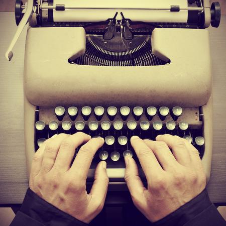 レトロな効果との古いタイプライターでタイピングの男