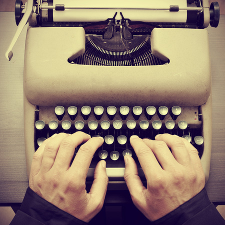 man typing on an old typewriter, with a retro effect Stock Photo