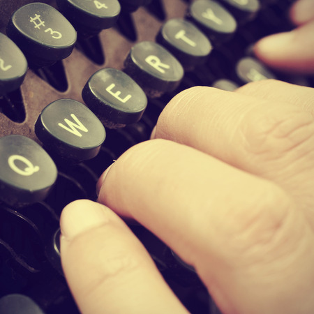 closeup of the hand of a man typing on an old typewriter, with a retro effect photo