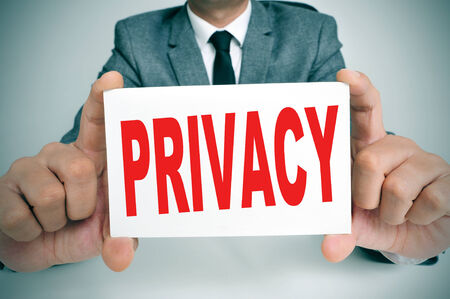 solicitor: a man wearing a suit showing a signboard with the text privacy written in it