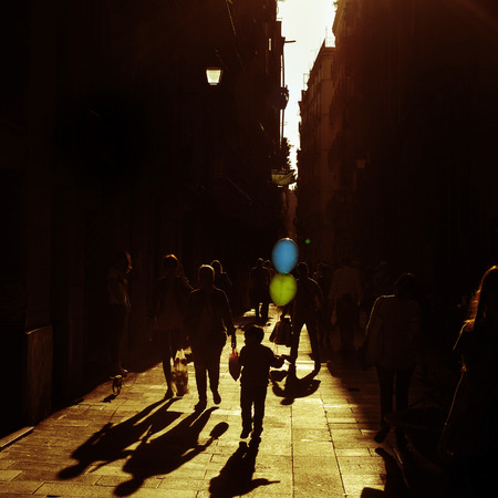 strangers: unrecognizable people walking in the street with sun backlight, highlighting a kid with colorful balloons, with a retro effect