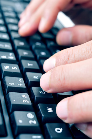 closeup of the hand of a man typing on computer keyboard photo