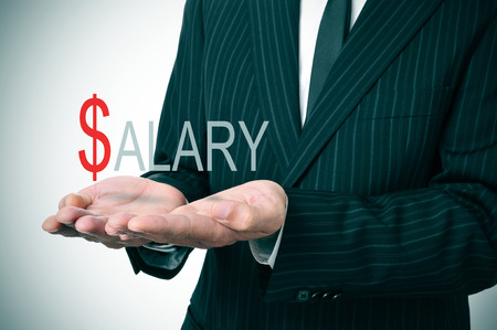 salaried: man wearing a suit holding the word salary in his hands