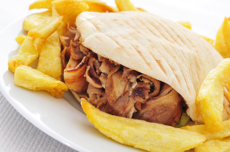 a doner kebab in a plate with french fries on a set table photo