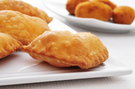 croquettes: closeup of a plate with some spanish empanadillas, small meat or tuna pies, served as tapas