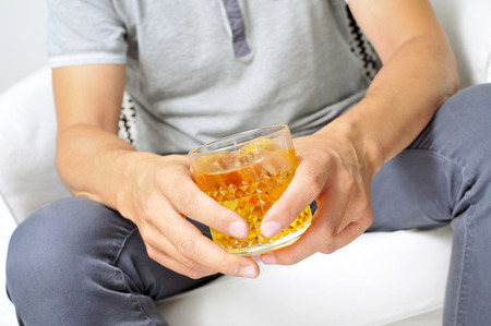 inebriation: young man hanging out with a glass of liquor Stock Photo