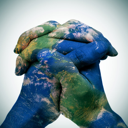 respeto: mapa del mundo en las manos entrelazadas de un hombre que forma un globo Foto de archivo