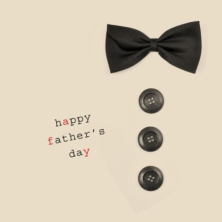 frase: condenar a padres d�a feliz y una pajarita y botones que representan a un hombre, sobre un fondo de color beige Foto de archivo