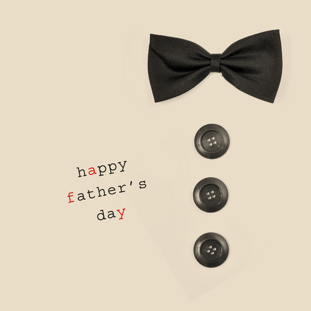 sentence happy fathers day and a bow tie and buttons depicting a man, on a beige background Stock Photo