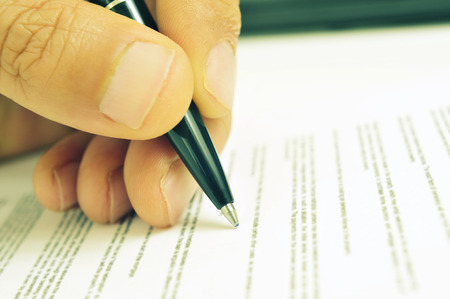 signer: closeup of the hand of a man ready to sign a document with a pen, with a retro filter effect