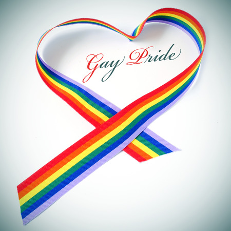 a rainbow ribbon forming a heart and the text gay pride Stock Photo