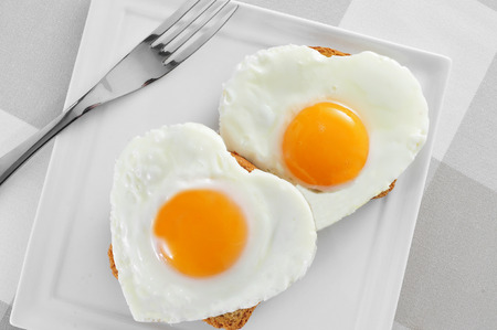 some heart-shaped fried eggs on toasts in a plate, on a set table photo