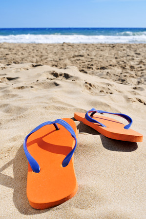 flipflops: a pair of orange flip-flops on the sand of a beach