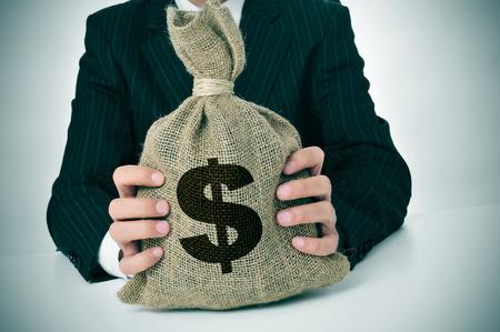 a man wearing a black suit holding a burlap money bag photo