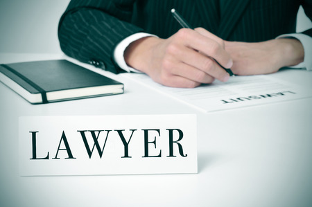 litigation: a man in his desk with a nameplate in front of him with the word lawyer written in it