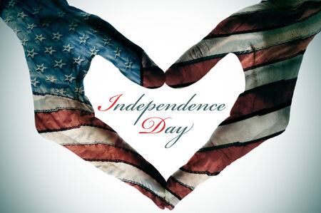 man hands patterned with the flag of the United States forming a heart and the sentence independence day photo