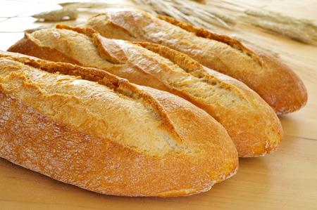 panino: primer plano de algunos baguettes demi o bollos de pan sobre una mesa de madera