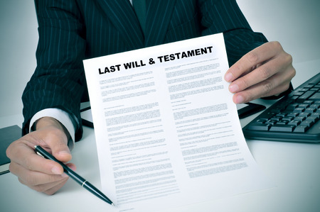 dispositions: hombre de traje que muestra que el testador debe firmar en un �ltimo documento de testamento Foto de archivo